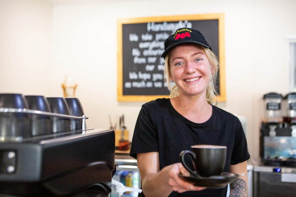 Smiling young woman handing you a coffee